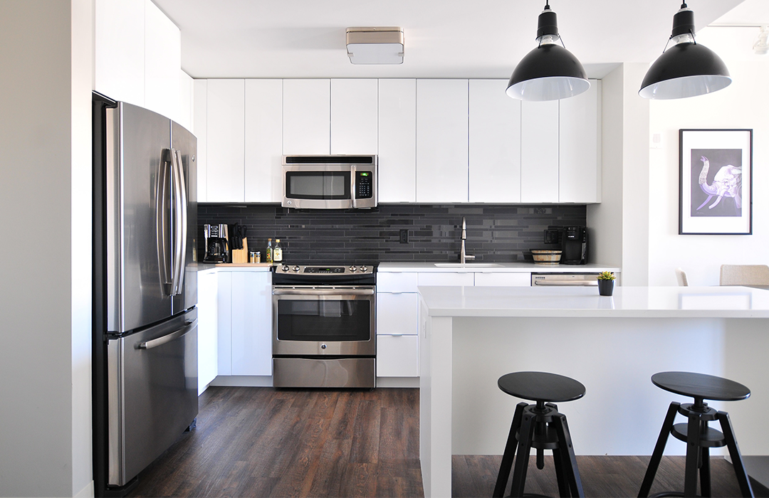 An elegant modern kitchen with steel appliances and black stools at a bar counter; full service property management