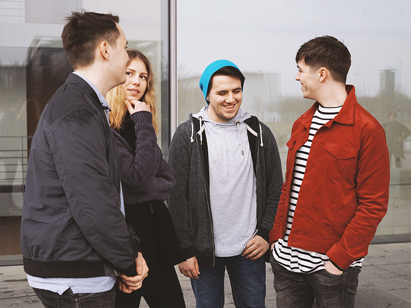 Four teenagers who are part of the community give back stand in a circle and talk