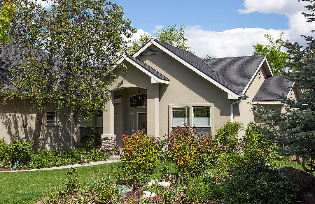 A beige rental home tucked away behind flowering shrubs; full service property management