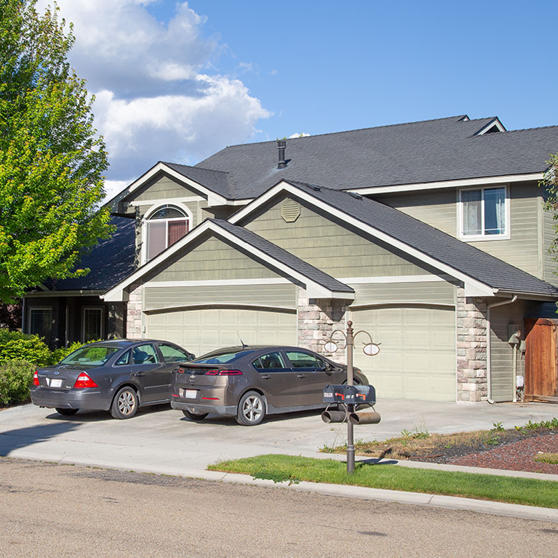 A green home with a two car garage and stone accents; property management