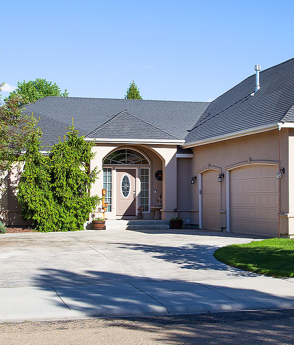 A beige single-story home with a two car garage available through tenant services