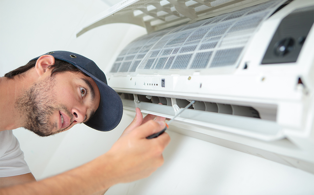 A man works on an air conditioner; summer property maintenance