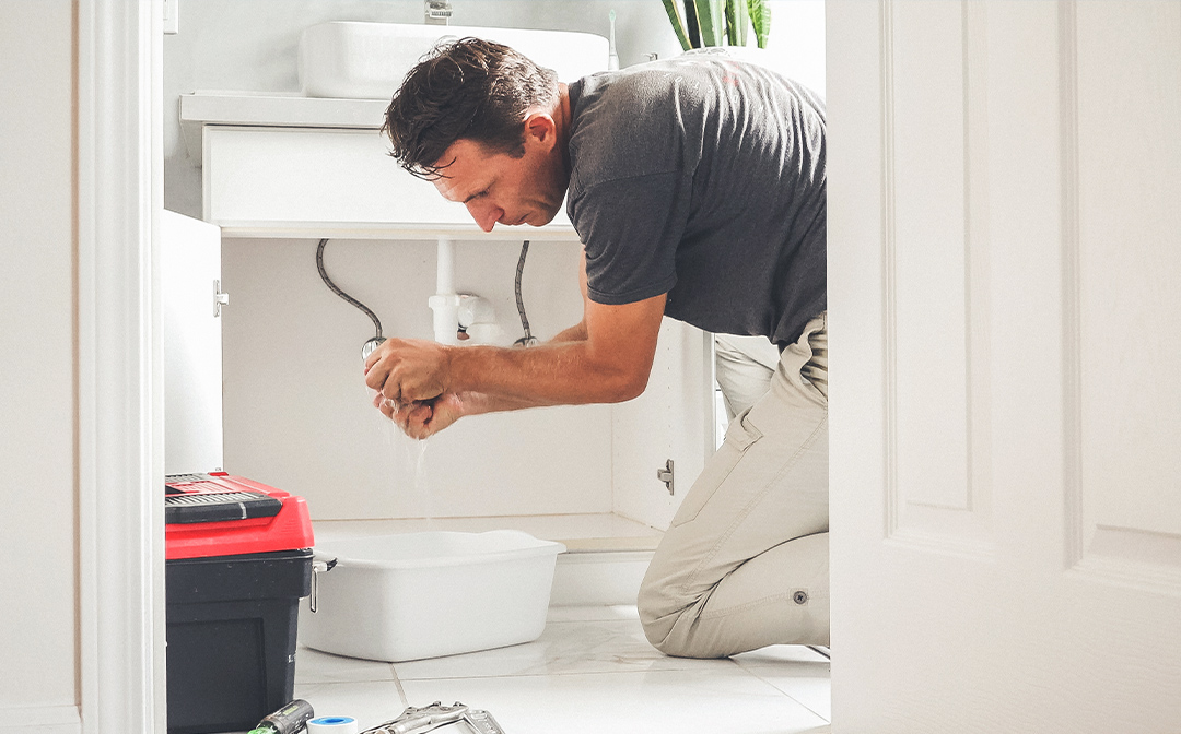 A man repairing a bathroom sink; what does a property management company do